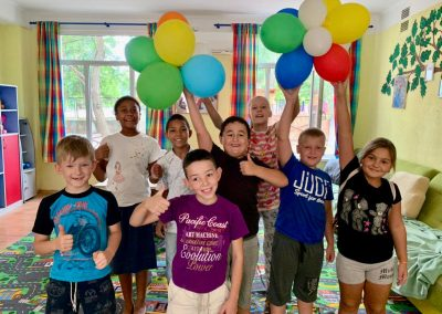 Children happy in a group, holding up balloons