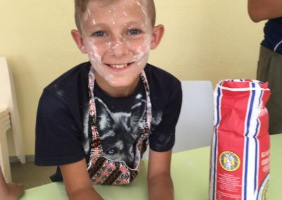 Boy in cooking workshop, with flour on his face smiling