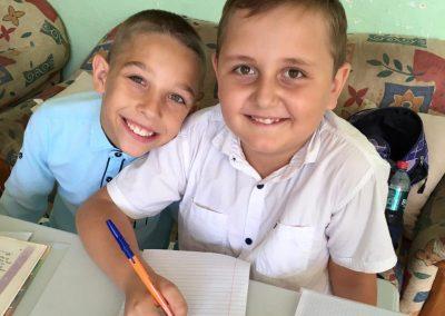 Boys doing school work together smiling