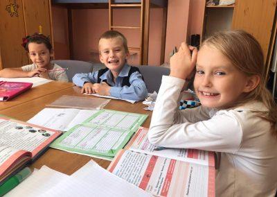 Children doing school work together smiling
